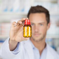 Closeup of a blurred male pharmacist holding out tablets in bottle at drugstore